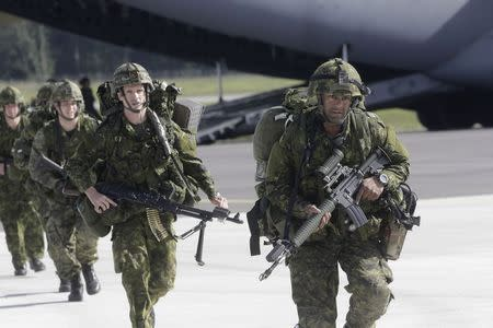 "U.S.173 airborne brigade soldiers leave a C-17 aircraft during the ""Steadfast Javelin II"" military exercise in the Lielvarde air base, September 6, 2014. REUTERS/Ints Kalnins"