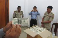 Police and court officials examine notes from a seized haul of $7.16 million in counterfeit hundred-dollar bills, in Battambang September 30, 2014. REUTERS/Andrew RC Marshall