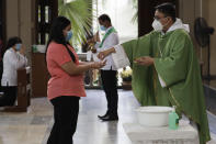 Catholic priest Fr. Ian Espartero distributes communion during Mass to only a few parishioners as a measure to prevent the spread of COVID19 at the Our Lady of Consolation Parish on Sunday, Aug. 2, 2020, in Quezon city, Philippines. Coronavirus infections in the Philippines continues to surge Sunday as medical groups declared the country was waging a losing battle against the contagion and asked the president to reimpose a lockdown in the capital. (AP Photo/Aaron Favila)