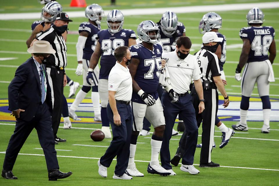 Cameron Erving walks off the field with help from Cowboys trainers.