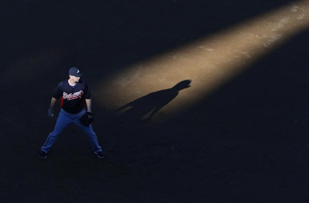 Atlanta Braves third baseman Chris Johnson stands in a shaft of light during batting practice before Game 4 in the National League baseball division series against the Los Angeles Dodgers, Monday, Oct. 7, 2013, in Los Angeles. (AP Photo/Jae C. Hong)