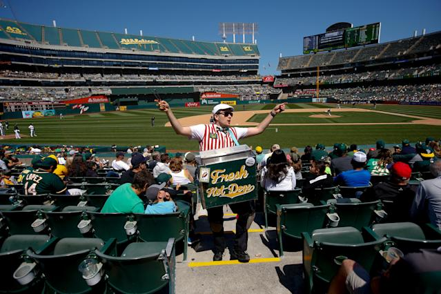 """A hot dog vendor sells hot dogs in the stands during an <a class=""""link rapid-noclick-resp"""" href=""""/mlb/teams/oakland/"""" data-ylk=""""slk:Oakland Athletics"""">Oakland Athletics</a> game in 2019. Concessions workers are one of the groups that could be financially devastated by the coronavirus-induced shutdown of baseball. (Photo by Michael Zagaris/Oakland Athletics/Getty Images)"""