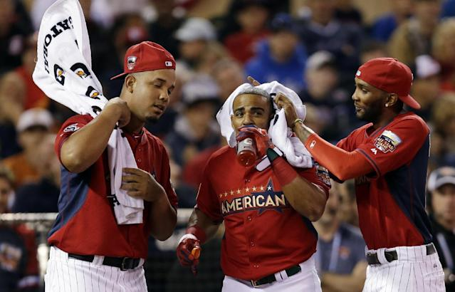 Teammates cool off American League's Yoenis Cespedes, of the Oakland Athletics, center, between pitches during the MLB All-Star baseball Home Run Derby, Monday, July 14, 2014, in Minneapolis. (AP Photo/Jeff Roberson)