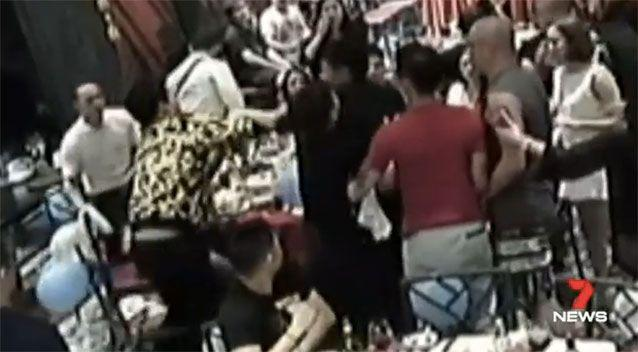 Ma, above left in yellow and black, is seen pushing another man. Picture: 7 News