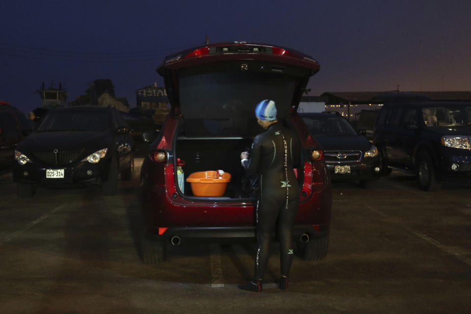 An open water swimmer gets ready by her car on Pescadores beach where swimming in the sea is booming while pools are closed due to the COVID-19 pandemic in Lima, Peru, before sunrise Tuesday, April 27, 2021. One of the few sporting disciplines that have been maintained during the coronavirus pandemic is swimming, which due to the closure of the swimming pools, has moved to the open sea. (AP Photo/Martin Mejia)