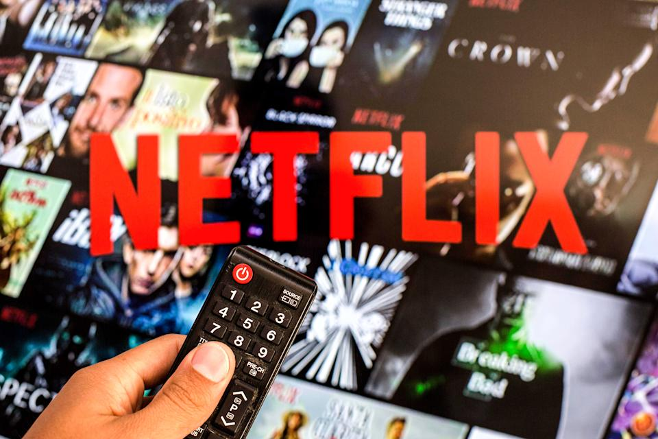 SPAIN - 2021/07/13: In this photo illustration a close-up of a hand holding a TV remote control seen displayed in front of the Netflix logo. (Photo Illustration by Thiago Prudencio/SOPA Images/LightRocket via Getty Images)