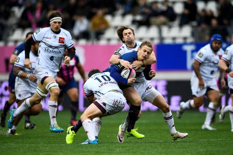 Stade Francais' fly half Jules Plisson (C) is tackled during the French Top 14 rugby union match between Stade Francais and Union Bordeux Begle, on March 5, 2017 at the Jean Bouin Stadium in Paris