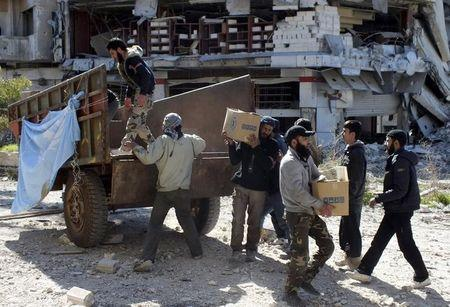 Men unload boxes of U.N. humanitarian aid at a besieged area of Homs