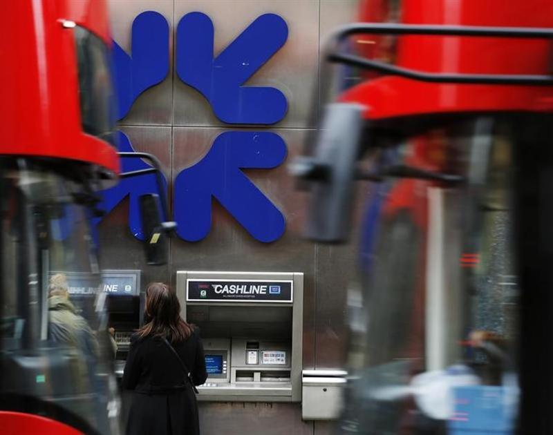 People stand near a branch of Royal Bank of Scotland (RBS) in London