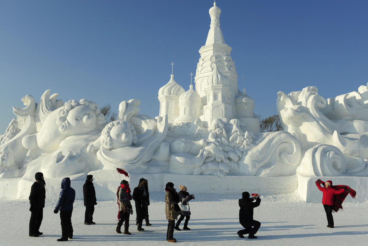 Tourists take pictures in front of a snow sculpture ahead of the 13th Harbin Ice and Snow World in Harbin, Heilongjiang province December 26, 2011. The Harbin International Ice and Snow Festival will be officially launched on January 5, 2012. REUTERS/Sheng Li (CHINA - Tags: ENVIRONMENT SOCIETY)