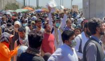 FILE PHOTO: Crowds of people show their documents to U.S. troops outside the airport in Kabul