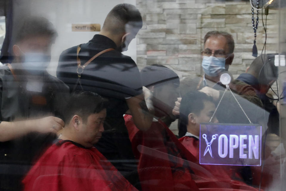 FILE - In this Monday, April 12, 2021 file photo, customers have their hair cut at a busy hairdresser in London, as the government takes the next step on its lockdown-lifting road map. Thanks to an efficient vaccine roll out program and high uptake rates, Britain is finally saying goodbye to months of tough lockdown restrictions. From Monday May 17, 2021, all restaurants and bars can fully reopen, as can hotels, cinemas, theatres and museums, and for the first time since March 2020, Britons can hug friends and family and meet up inside other people's houses. (AP Photo/Frank Augstein, File)