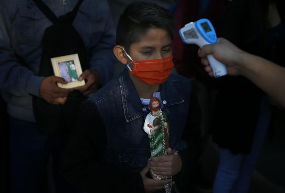 A boy holding a statue of Saint Jude and wearing a protective face mask amid the new coronavirus, stands still as his temperature is measured before entering the San Hipolito Catholic church, during the annual pilgrimage honoring Jude, the patron saint of lost causes, in Mexico City, Wednesday, Oct. 28, 2020. Thousands of Mexicans did not miss this year to mark St. Jude's feast day, but the pandemic caused Masses to be canceled and the rivers of people of other years were replaced by orderly lines of masked worshipers waiting their turn for a blessing. (AP Photo/Marco Ugarte)