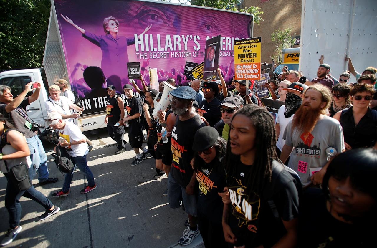 Protestors against police violence make their through the city pass an advertisement for a film featuring an image of Democratic Presidential Hillary Clinton near the Republican National Convention in Cleveland, Ohio, U.S., July 19, 2016.  REUTERS/Jim Urquhart