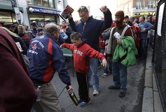 FILE - In this Oct. 30, 2013 file photo, Jeffrey Corbett, top, and his son Joseph, 9, center, both of Arlington, Mass., raise their arms as they pass through security outside Fenway Park before Game 6 of baseball's World Series between the Boston Red Sox and St. Louis Cardinals, in Boston. Baseball fans should expect to go through a metal detector to see their team play in 2014. MLB security director John Skinner says at a panel discussion at Harvard that the commissioner's office plans to recommend walkthrough metal detectors. (AP Photo/Steven Senne, File)