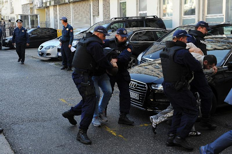 Men are escorted by Montenegrin police officers to the special court in Podgorica on October 16, 2016 (AFP Photo/SAVO PRELEVIC                   )