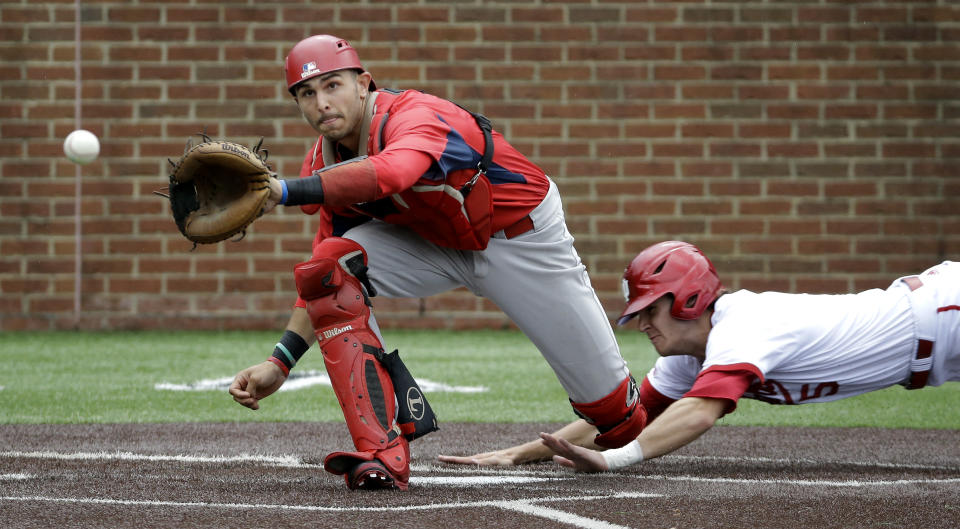 Radford catcher Josh Reavis, left, waits for the throw as Brian Wilhite, right, scores from third after a pickoff-attempt at first base in the fifth inning of an NCAA regional college baseball game Sunday, May 31, 2015, in Nashville, Tenn. Radford won 5-3. (AP Photo/Mark Humphrey)