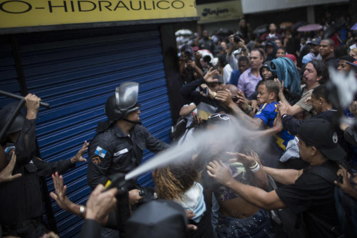 A woman is pepper sprayed as residents of Pavao-Pavaozinho slum clash with riot police during a protest against the death of Douglas Rafael da Silva Pereira after his burial in Rio de Janeiro, Brazil, Thursday, April 24, 2014. The protest followed the burial of Pereira, whose shooting death sparked clashes Tuesday night between police and residents of the Pavao-Pavaozinho slum. (AP Photo/Felipe Dana)