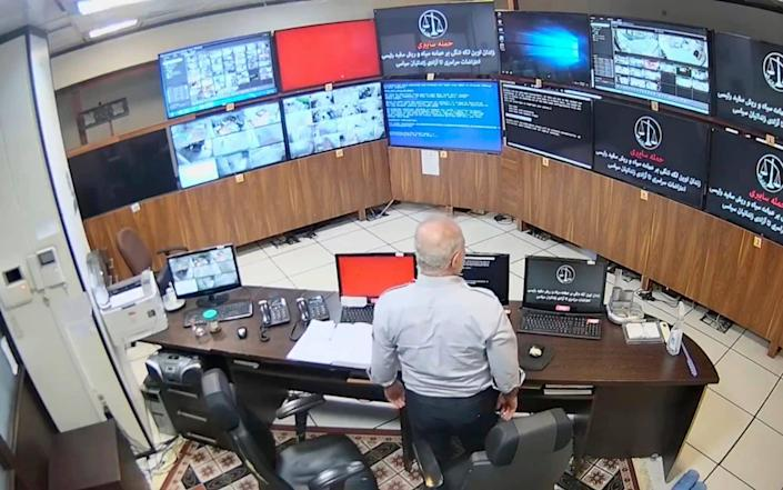 A prison employee looks on as surveillance screens in the control room are taken over by the hacker group. - The Justice of Ali