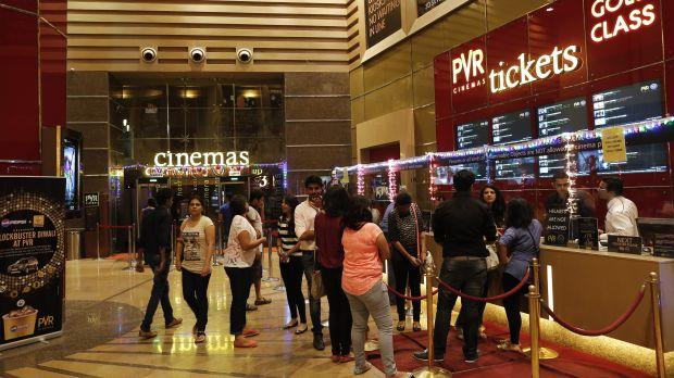 Cinema-goers wait to collect their tickets at a PVR Multiplex in Mumbai