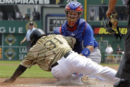 Chicago Cubs catcher Koyle Hill, top, puts the tag on Pittsburgh Pirates' Jose Tabata (31) during the first inning of a baseball game in Pittsburgh, Sunday, May 27, 2012. Tabata was attempting to score from third on a fielder's choice by Pirates' Andrew McCutchen. (AP Photo/Gene J. Puskar)