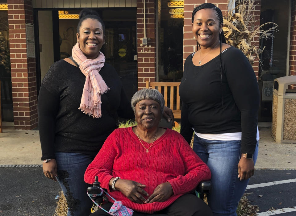 In this Nov. 28, 2019, photo provided by the Burrough family, Bessie Burden, center, poses with her daughters Theresa Burrough, left, and Lashieka Mitchell outside the Westbury Conyers nursing home in Conyers, Ga. Burden died Oct. 22, 2020, after becoming infected with the coronavirus during an outbreak at the nursing home. Burden's daughters blame the home for their mother's death, saying administrators kept the family in the dark about Burden being exposed to the virus and quarantined as a presumptive case. But the state has essentially blocked them from going to court. (Leah Burrough via AP)