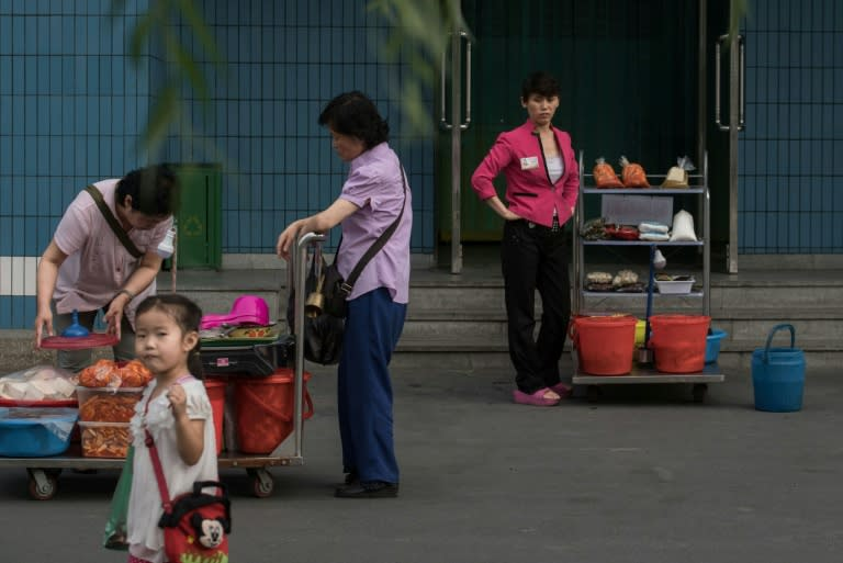 Street vendors wait for customers in Pyongyang, where economic change is quietly taking place, even as North Korean authorities insist the philosophy of founder Kim Il-Sung remains the rule