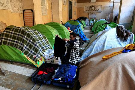 A woman folds clothes next to her tent in the portico of the Basilica of the Santi Apostoli, where she lives after being evicted from an unused building along with other families in August 2017, in Rome, Italy January 29, 2018.  REUTERS/Tony Gentile