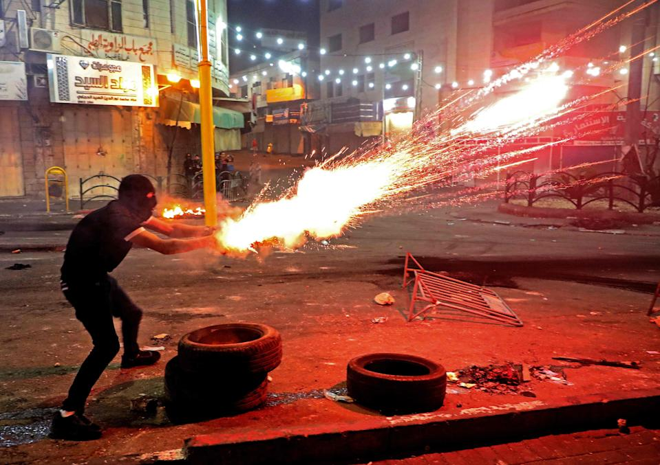 A Palestinian protester launches flares amid clashes with Israeli soldiers in the city centre of Hebron in the West Bank (AFP via Getty Images)