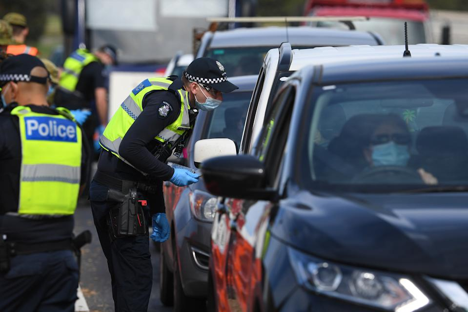 Victoria Police and ADF personnel are seen at work at a roadside checkpoint near Donnybrook, Victoria.