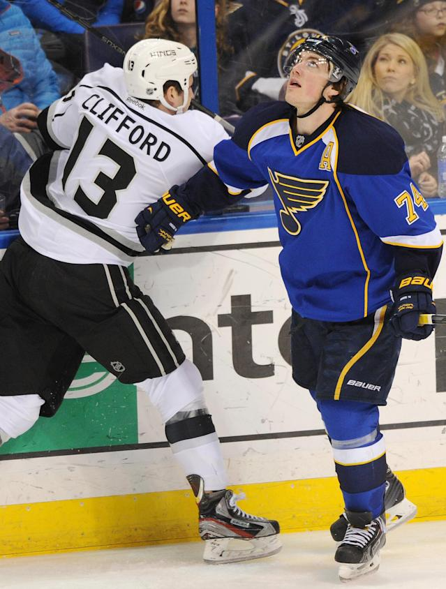 St. Louis Blues' T.J. Oshie (74) checks Los Angeles Kings' Kyle Clifford (13) and looks for the puck during the third period of an NHL hockey game on Thursday, Jan. 2, 2014 in St. Louis. (AP Photo/Bill Boyce)