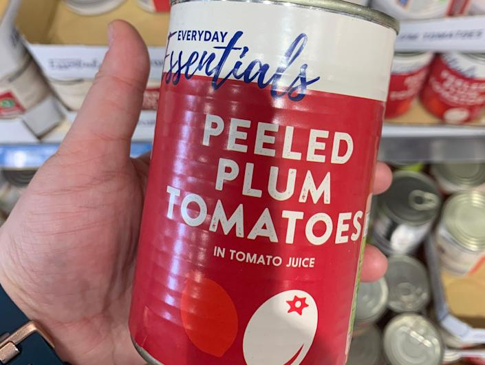 hand holding a can of tinned tomatoes at aldi