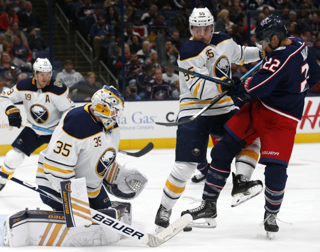 Buffalo Sabres goalie Linus Ullmark, left, of Sweden, stops a shot in front of Columbus Blue Jackets forward Sonny Milano, right, as Sabres defenseman Rasmus Ristolainen, of Finland, defends during the second period of an NHL hockey game in Columbus, Ohio, Monday, Oct. 7, 2019. (AP Photo/Paul Vernon)