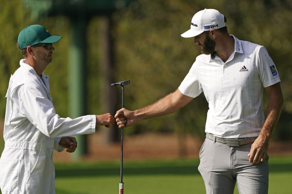 Dustin Johnson fist pumps his caddie Austin Johnson after a birdie putt on the third hole during the third round of the Masters golf tournament Saturday, Nov. 14, 2020, in Augusta, Ga. (AP Photo/Charlie Riedel)