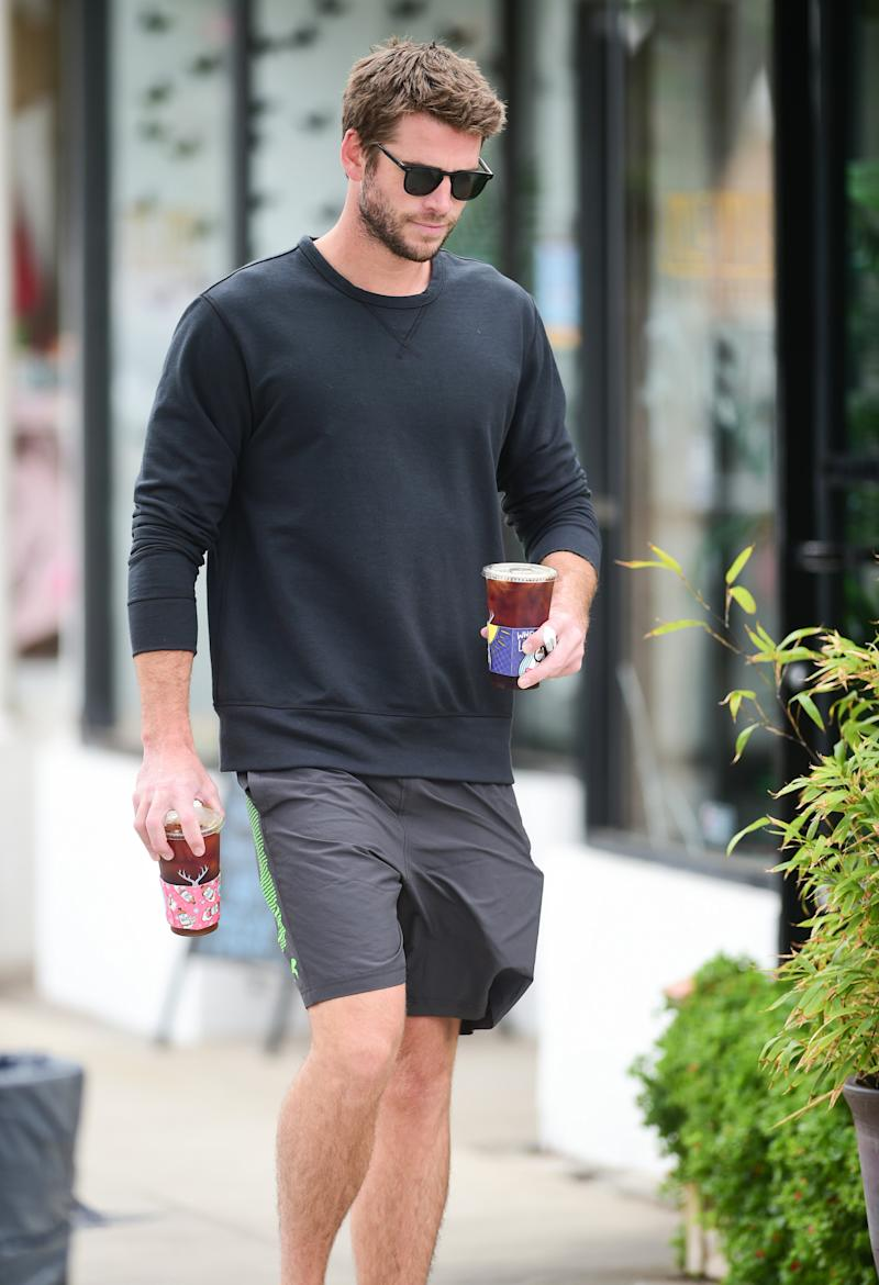 Liam Hemsworth holding a coffee in LA