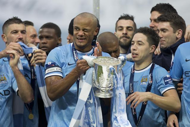 Manchester City players including captain Vincent Kompany, center left, celebrate after their 3-1 win against Sunderland in the League Cup Final at Wembley Stadium, London, England, Sunday March 2, 2014. (AP Photo/Jon Super)
