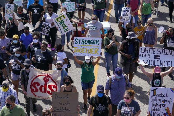 Hundreds march at a rally for Jacob Blake Saturday, Aug. 29, 2020, in Kenosha, Wis. Blake, 29, a Black man, was shot in the back seven times on Sunday by police in Kenosha. A family attorney said Blake was paralyzed. (AP Photo/Morry Gash)