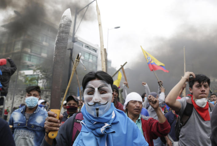 Anti-government protesters clash with police near the National Assembly in Quito, Ecuador, Tuesday, Oct. 8, 2019. Anti-government protests, which began when President Lenín Moreno's decision to cut subsidies led to a sharp increase in fuel prices, has persisted for days, and clashes led the president to move his besieged administration out of Quito. (AP Photo/Dolores Ochoa)