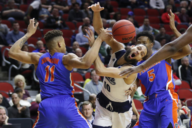 Nevada forward Caleb Martin, center, loses the ball while driving between Florida's Keyontae Johnson, left, and KeVaughn Allen, right, during a first round men's college basketball game in the NCAA Tournament, Thursday, March 21, 2019, in Des Moines, Iowa. (AP Photo/Charlie Neibergall)