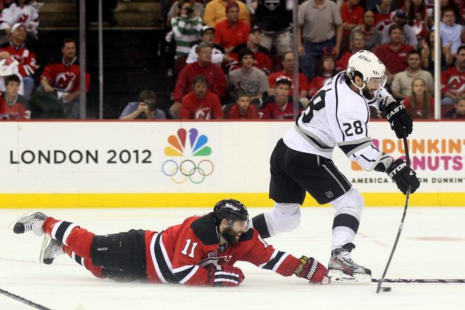 NEWARK, NJ - JUNE 09: Jarret Stoll #28 of the Los Angeles Kings handles the puck as Stephen Gionta #11 of the New Jersey Devils hits the ice during Game Five of the 2012 NHL Stanley Cup Final at the Prudential Center on June 9, 2012 in Newark, New Jersey.  (Photo by Elsa/Getty Images)