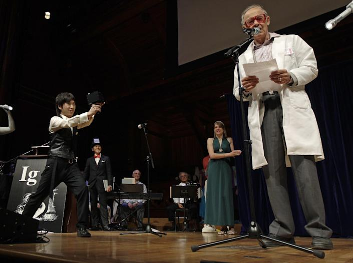 """Koji Tsukada, left, fires his invention the """"SpeechJammer"""" at 1986 Nobel Prize laureate for Chemistry Dudley Herschbach during a performance at the Ig Nobel Prize ceremony at Harvard University, in Cambridge, Mass., Thursday, Sept. 20, 2012. The Ig Nobel prize is an award handed out by the Annals of Improbable Research magazine for silly sounding scientific discoveries that often have surprisingly practical applications. (AP Photo/)"""