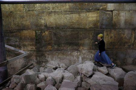 Israel Antiquities Authority archaeologist Tehillah Lieberman walks atop stones lying besides a part of the Western Wall, during a media tour revealing a theatre-like structure which was discovered during excavation works underneath Wilson's Arch in the Western Wall tunnels in Jerusalem's Old City October 16, 2017. REUTERS/Ronen Zvulun