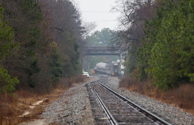 <p>A derailed Amtrak car can be seen up the tracks near a crossing after an early morning collision with a CSX freight train on February 4, 2018 in Cayce, South Carolina. (Photo: Logan Cyrus/AFP/Getty Images) </p>