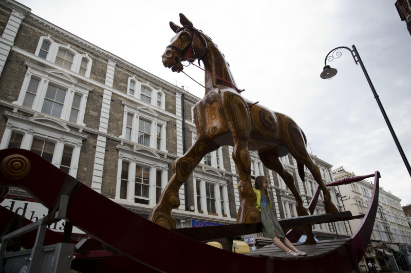 """Riva aged 6, poses for photographs beside a giant rocking horse during a photocall outside Christie's auction house in London, Monday, Aug. 5, 2013. The rocking horse, is estimated to fetch between 25,000 to 40,000 pounds (US dlrs 38,382 to 61,411 and 28,910 to 46,256 euro) in an """"Out of the Ordinary"""" sale on September 5. (AP Photo/Matt Dunham)"""