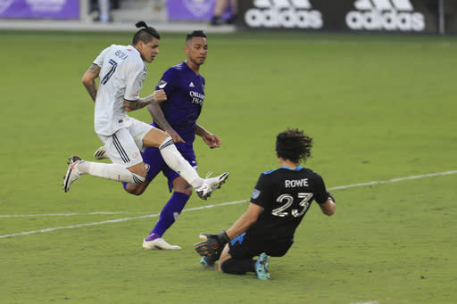 New England Revolution forward Gustavo Bou (7) scores a goal past Orlando City goalkeeper Brian Rowe (23) and defender Antonio Carlos (25) during the second half of an MLS playoff soccer match, Sunday, Nov. 29, 2020, in Orlando, Fla. (AP Photo/Matt Stamey)