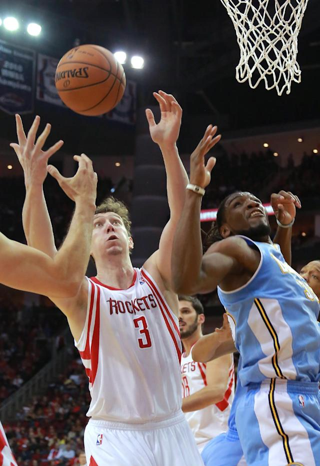 Houston Rockets center Omer Asik (3) and Denver Nuggets forward Kenneth Faried look for a rebound during the first half of an NBA basketball game in Houston on Sunday, April 6, 2014. (AP Photo/Richard Carson)