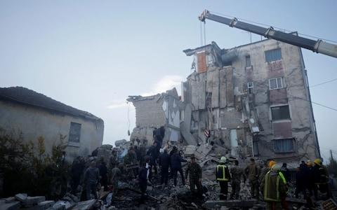 Emergency personnel work near a damaged building in Thumane, after an earthquake shook Albania - Credit: REUTERS