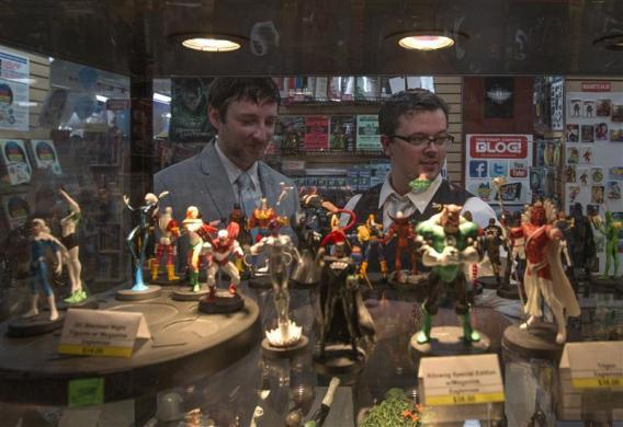Jason Welker (L) and Scott Everhart are photographed through a glass casing containing comic book characters after their wedding ceremony at a comic book retail shop in Manhattan, New York June 20, 2012.