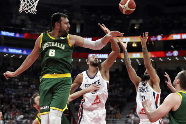 Andrew Bogut of Australia and Rudy Gobert, center, and Evan Fournier of France battle for the ball during their third-place match in the FIBA Basketball World Cup at the Cadillac Arena in Beijing, Sunday, Sept. 15, 2019. (AP Photo/Mark Schiefelbein)