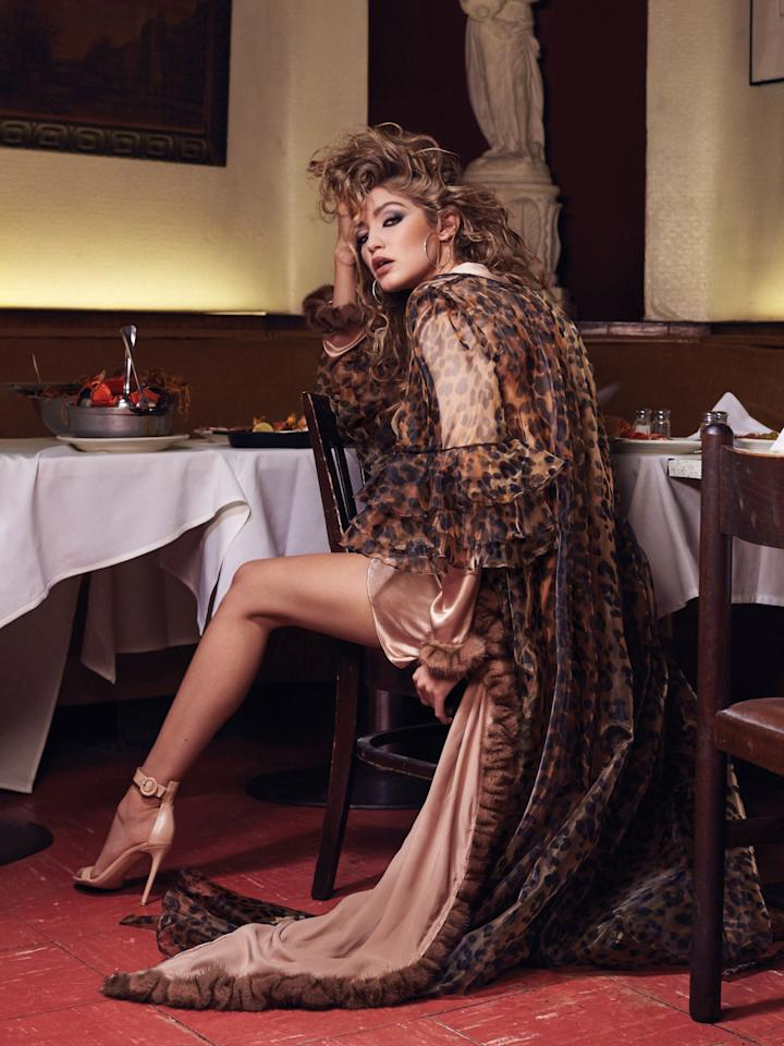"""<p>Gigi Hadid owes a lot to Carine Roitfeld. The editor-in-chief of <i>CR Fashion Book</i>first put the young model on the cover of her magazine three years ago — and now, Hadid's on<i> CR</i>once more. Last week, the 20-year-old <a href=""""https://www.instagram.com/p/BCI7c-NjCUs/?taken-by=gigihadid"""">shared a photo of Issue 8</a>, featuring her in a tight black corseted bodysuit, door knocker earrings, and permed hair accented with an American flag-patterned bow. And now, we've gotten our first look at the accompanying shoot — which sees a super sexy,'80s-inspired Hadid smoldering in what appears to be an Italian restaurant. <i>Mamma mia</i>, indeed! Hadid <a href=""""https://www.instagram.com/p/BCI7c-NjCUs/?taken-by=gigihadid"""">thanked Roitfeld for her support</a> on Instagram, writing,""""I know that my career would not be the same without Carine. Thank you for believing in and guiding me & for being an unequivocal mentor and friend; every day I get to work with you is an honor."""" Head to<i> <a href=""""http://www.crfashionbook.com/book/gigi-hadid-cr-8/"""">CR Fashion Book</a></i> for more of her cover spread.</p>"""